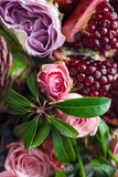 A bouquet of red and pink roses, peonies with grapes and pomegranate closeup Royalty Free Stock Images