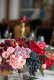 The bouquet of red and pink roses, peonies with grapes and pomegranates in the Dutch style Stock Image