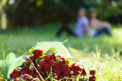 Bouquet red rose in the green grass. Couple in the background Royalty Free Stock Photography