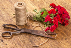 Bouquet of Red Roses, ball of Twine and Old Rusty Scissors on Wo Stock Photos