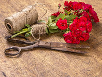 Bouquet of Red Roses, ball of Twine and Old Rusty Scissors on Wo Stock Photo