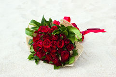 Bouquet of red roses on the beach Royalty Free Stock Photography