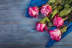 Bouquet of red roses on a blue. Wooden background royalty free stock images