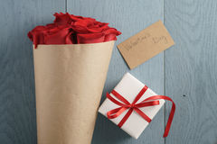 Bouquet of red roses on blue wood table with gift and valentines day paper card from above Stock Images