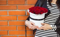 Bouquet of red roses in a box in the hands of the girl. royalty free stock photo