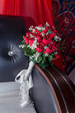A bouquet of red roses on a brown sofa on a scarlet background with Arabic ornaments Stock Images