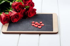 Bouquet of red roses and chalkboard on white wooden board. Space for text. Bouquet of red roses and chalkboard on the white wooden board. Space for text Royalty Free Stock Photography