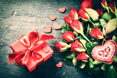 Bouquet of red roses with decorative heart and gift box Stock Image