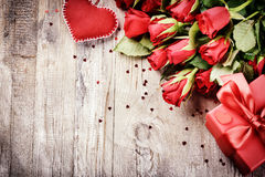 Bouquet of red roses with decorative heart and present. St Valen Stock Photography