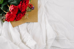 A bouquet of red roses, envelope with congratulation on a background of linen. Good morning darling Royalty Free Stock Photo