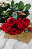 A bouquet of red roses, envelope with congratulation on a background of linen. Good morning darling Royalty Free Stock Image