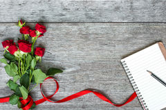 Bouquet of red roses flowers with blank notebook and pencil Royalty Free Stock Images