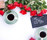 A bouquet of red roses and fresh aromatic tea for a romantic breakfast. Words of love on a note and a gift with flowers. Valentine. A bouquet of red roses and royalty free stock photography