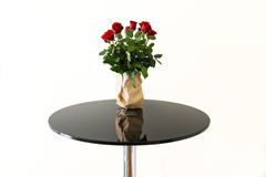 Bouquet of red roses in grey paper vase on table Royalty Free Stock Photography