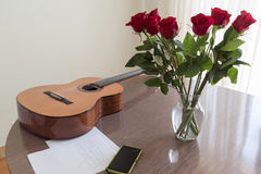 Bouquet of red roses and guitar. Still life with a guitar, a bouquet of roses, a smartphone and musical notes Royalty Free Stock Photography