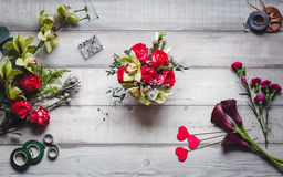 Bouquet of red roses, hearts, callas, carnations and ribbons on the table Royalty Free Stock Photography