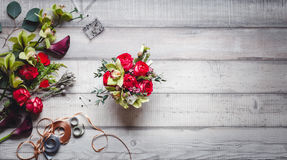 Bouquet of red roses, hearts, callas, carnations and ribbons on the table Royalty Free Stock Photo