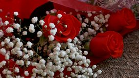 Bouquet of red roses lying on chair in the room. Bouquet  of red roses lying on chair in the room stock footage