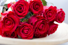 Bouquet of red roses lying on a plate. Bouquet of red roses on plate Royalty Free Stock Photos