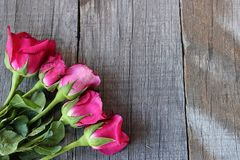 Bouquet of red roses on old wooden board background with copy space for massage. Valentine`s day concept or wedding card Stock Photo