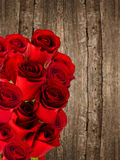 Bouquet of red roses over wooden background Royalty Free Stock Photo