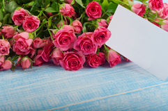 Bouquet of red roses with a postcard Royalty Free Stock Images