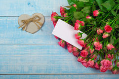 Bouquet of red roses with a postcard Royalty Free Stock Photo