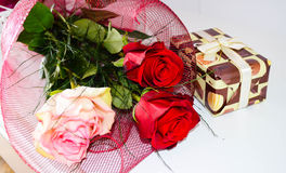 Bouquet of   red roses and present  on a  white  background Royalty Free Stock Image