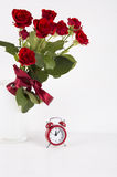 Bouquet of red roses with red alarm clock on white background Royalty Free Stock Image