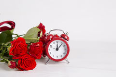 Bouquet of red roses with red alarm clock on white background Royalty Free Stock Images