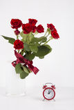 Bouquet of red roses with red alarm clock on white background Stock Image