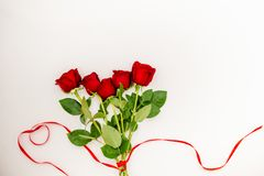 Bouquet of red roses with a red ribbon and an evelope. Bouquet of red roses with a red ribbon. march woman's day, holiday. Flowers on a white background stock image