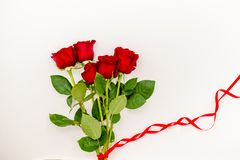 Bouquet of red roses with a red ribbon and an evelope. Bouquet of red roses with a red ribbon. march woman's day, holiday. Flowers on a white background stock photo