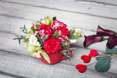 Bouquet of red roses in red vase, hearts, callas on table, space for text Stock Image