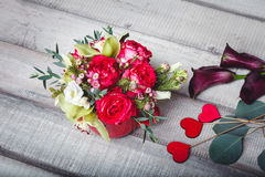 Bouquet of red roses in red vase, hearts, callas on table, space for text Stock Photo