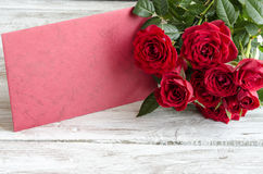Bouquet of red roses with red wooden plank on table Royalty Free Stock Images