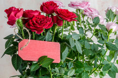 Bouquet of red roses with red wooden plank on table Stock Image