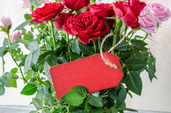 Bouquet of red roses with red wooden plank on table Royalty Free Stock Image