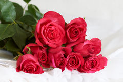 Bouquet of red roses - series of red roses. Bouquet of red roses on a white dress Royalty Free Stock Image