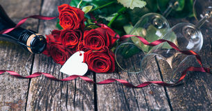 Bouquet of red roses, two glasses, bottle of wine, gift box with tag on vintage wooden board. Valentines day. Stock Photos
