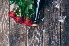 Bouquet of red roses, two glasses, bottle of wine, gift box with tag on vintage wooden board. Valentines day. Top view. Royalty Free Stock Images