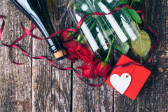 Bouquet of red roses, two glasses, bottle of wine, gift box with tag on vintage wooden board. Valentines day. Top view. Royalty Free Stock Photography