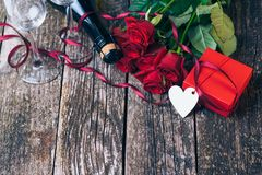 Bouquet of red roses, two glasses, bottle of wine, gift box with tag on vintage wooden board. Valentines day. Royalty Free Stock Image