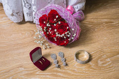 A bouquet of red roses, wedding dress, wedding rings in red box. Bride earrings and bracelet on a wooden background, preparation for the wedding Stock Photo