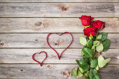 Bouquet of red roses on wood background with hearts from ribbon. Royalty Free Stock Image