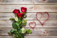 Bouquet of red roses on wood background with hearts from ribbon. Royalty Free Stock Photo