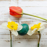 Bouquet of red spring tulip, daffodils and handmade colorful painted easter eggs against rustic wooden background Stock Photography