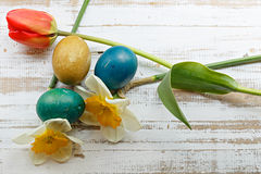 Bouquet of red spring tulip, daffodils and handmade colorful painted easter eggs against rustic wooden background Royalty Free Stock Images