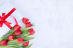 A bouquet of red tulips and a box with a bow on a white background. Surprise and flowers for a romantic holiday. A gift for mom or. Dad stock image