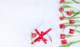 A bouquet of red tulips and a box with a bow on a white background. Surprise and flowers for a romantic holiday. A gift for mom or. Dad royalty free stock images